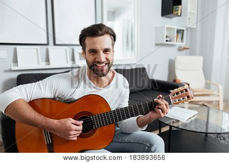 Picture of young happy man sitting on sofa indoors at home while playing on guitar. Looking at camera.