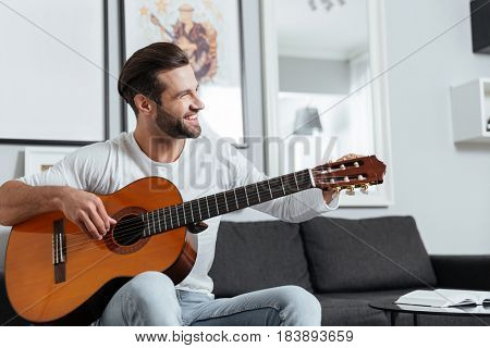 Photo of young happy man sitting on sofa indoors at home while playing on guitar. Looking aside.