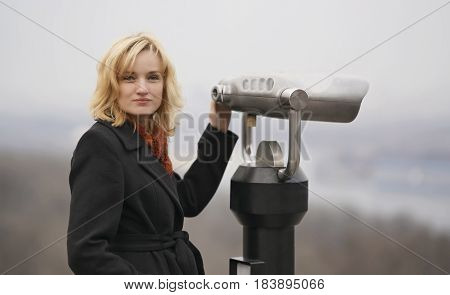 Beautiful blonde stand on the observation deck with a large of binoculars. She dressed in a dark coat and a bright scarf. She is looking at the camera, the background behind is blurred