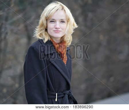 Portrait of young blonde on a dark blurred background. She dressed in a black long coat with a orange shawl around her neck. She holds her hands in pockets