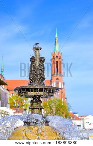 City fountain with bronze sculpture of two boys on Central square of Kosciusko Market. On background Cathedral Basilica of Assumption of Blessed Virgin Mary in Bialystok Poland