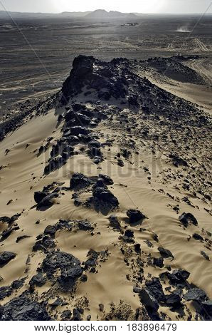 BLACK DESERT - EGYPT - DECEMBER 2010: View from basalt-sand hill on the moving off-road vehicle. Sunset in the desert. Vertical photo.