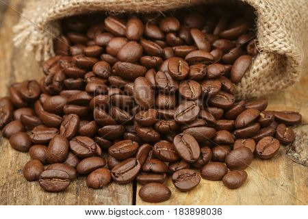Coffee beans closeup on wooden table. Selective focus