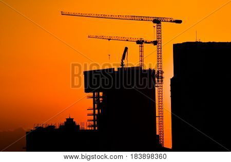 Silhouette of building under construction and the construction crane or power crane sunset time.