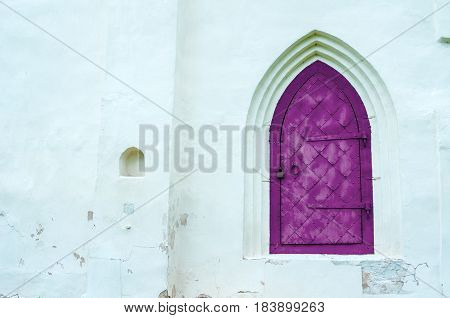 Architecture view of architecture elements- aged dark magenta metal forged door with arcade on the white stone wall. Architecture background with architecture details.