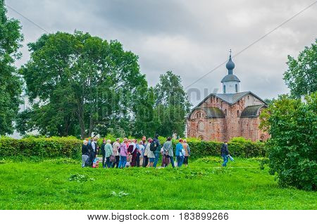 VELIKY NOVGOROD RUSSIA - AUGUST 19.2016. Tourists at the excursion in Veliky Novgorod Russia. Paraskeva Pyatnitsa Church at Yaroslav Courtyard in Veliky Novgorod Russia.