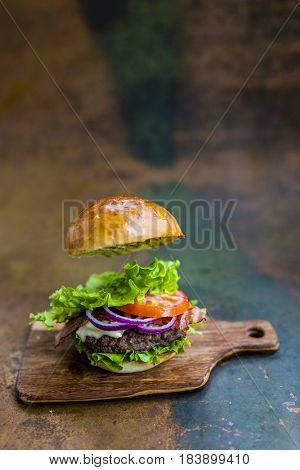Tasty grilled beef burger with spinach lettuce and blue cheese served with french fries on wooden table with copyspace, blackboard in background.