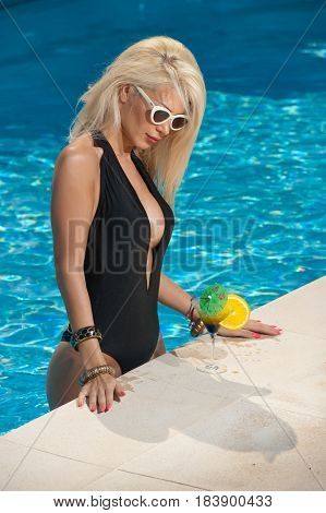 Beautiful sensual blonde with fashionable sunglasses relaxing in the pool with a juice. Attractive long hair woman in black low-cut swimsuit at swimming pool. Fair hair young female, summer shot.
