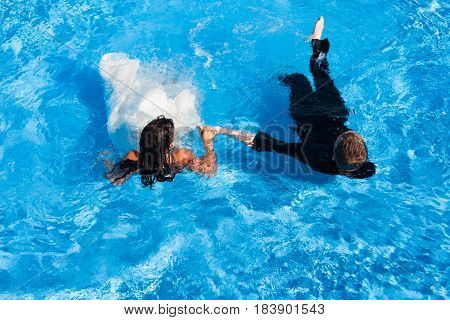 Newly wed bride and groom with their bridal dress and suit lying in a swimming pool unrecognizable shot from above.