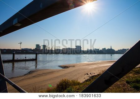 The sun shinging in the blue summersky over the river and the riverside as seen from the other side of the river