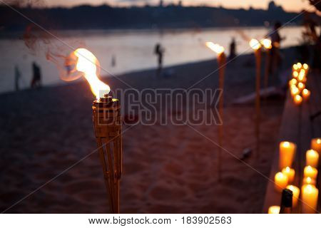 night lit torch on the beach near the water, people in the background