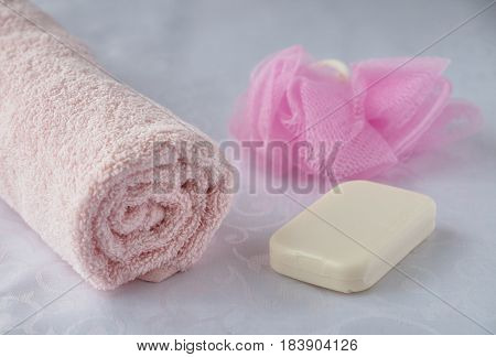 Colored pink towel washcloth and soap on a white background
