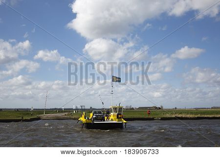 Eemdijk, the Netherlands - march 3, 2016; Yellow ferry is crossing the river Eem at Eemdijk, the Netherlands
