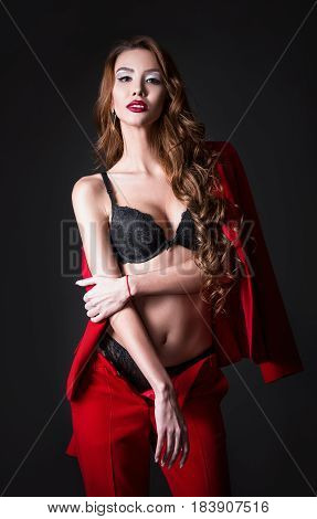 Studio fashion shot: a charming sexy young woman in black lingerie and red costume