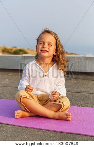 Beautiful happy baby is singing on the yoga mat