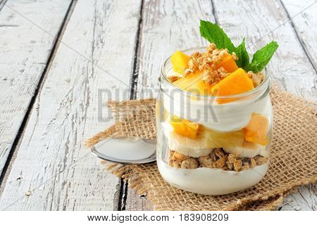 Tropical Mango And Pineapple Parfait In A Mason Jar On A Rustic White Wood Background