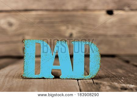 Blue Dad Distressed Metallic Sign Against A Rustic Wood Background