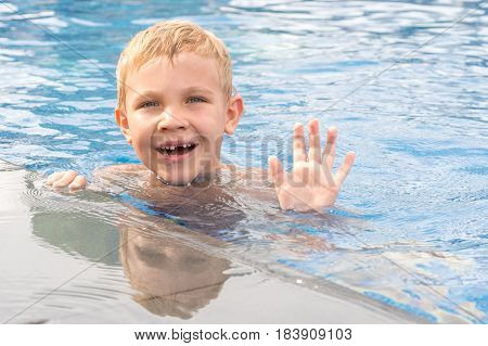 Funny boy swimming and playing in a pool