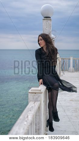 Emotional beautiful brunette girl in a black dress posing on the pier. Sea and grey clouds on background. She is waiting for somebody.