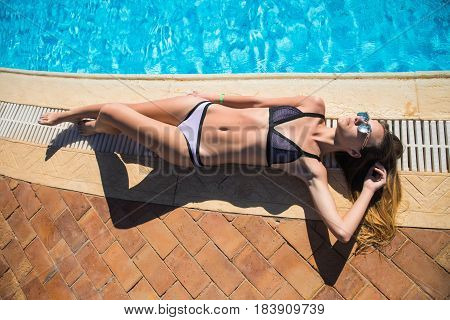 Beautiful Sexy Luxurious Girl Lies On The Edge Of The Swimming Pool Sunbathing