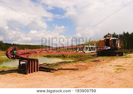 Abondened quarry crane. Sand quarry. Industrial rusty concept.