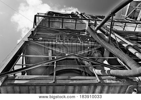 Industrial metal tower. Sand quarry aggregate. Black & white photo.