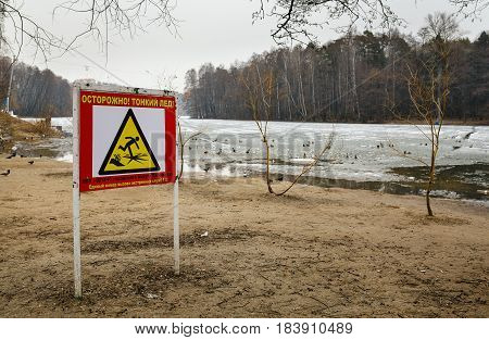 A thin ice warning sign on a city beach with inscription in Russian: beware thin ice.