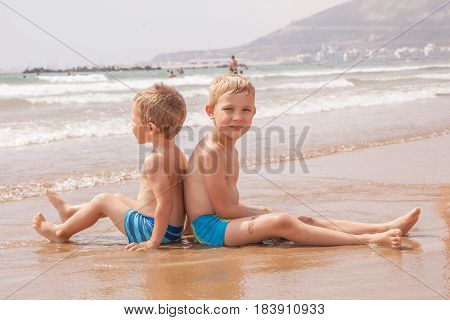 Two cute adorable funny little brothers boys sitting on the beach ocean sea travel