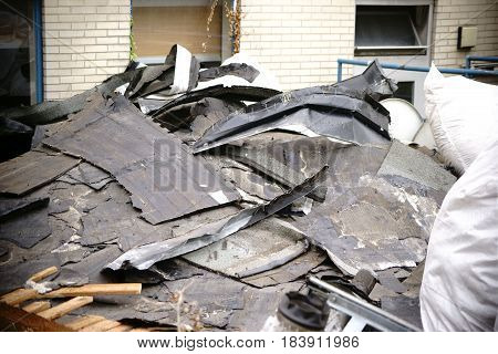 The close-up of debris from rubble and the false ceiling and and the tarred ceiling of a truss.