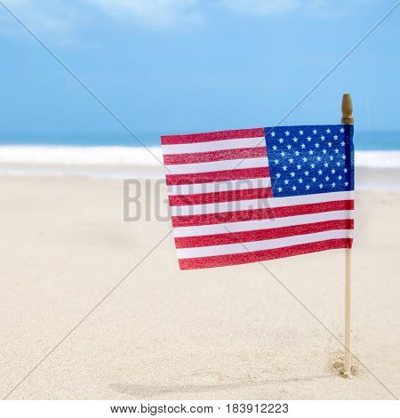 Independence Day USA background with flag on the sandy beach near the ocean American patriotic concept square Instagram format