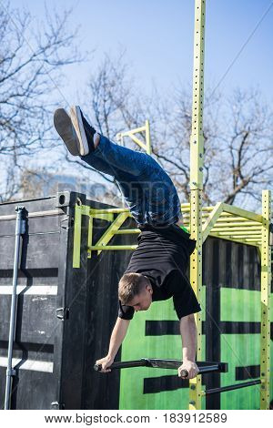 Young Athlete doing a Hand Stand On Parallel Bars In An Outdoor Gym - Street Workout Exercises. Man's flexibility.