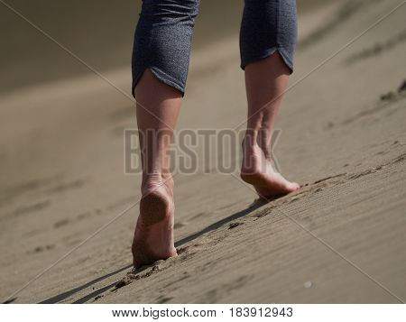 bare feet of young woman jogging/walking on the beach at sunrise