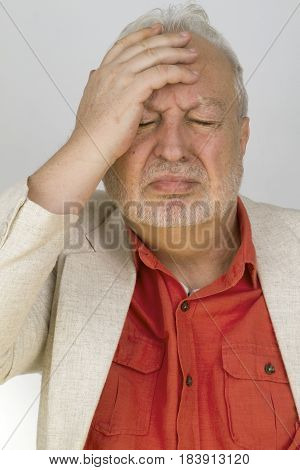 Doubtful senior man puts his hand on his forehead - on bright background