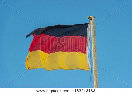 German waving flag on light blue background
