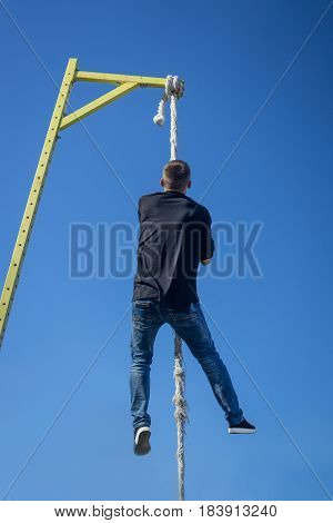 Young Athlete climbing up the Fitness rope. climb exercise in outdoor crossfit gym. Sky background