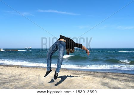 portrait of young parkour man doing flip or somersault on the beach. Freezed moment of flip.