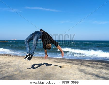 portrait of young parkour man doing flip or somersault on the beach