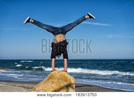 Young Athlete doing handstand on the stone of beach. Street workout. Balance concept.