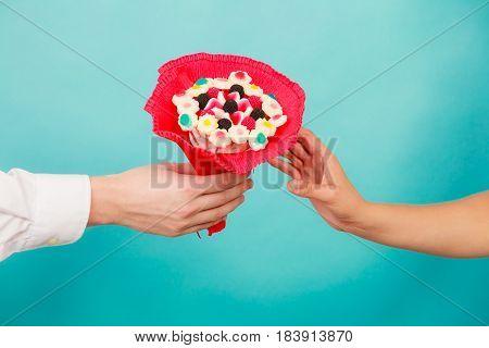 Closeup Of Man Giving Woman Candy Bunch Flowers.