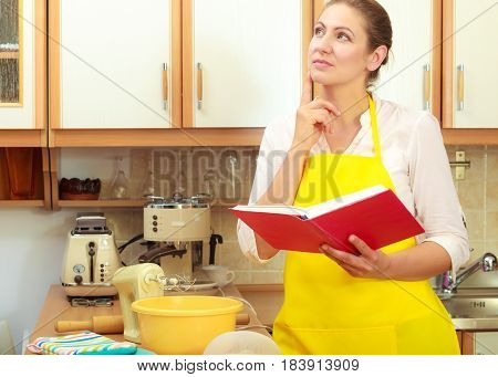 Creative housewife planning dinner supper. Middle aged woman chef with cookbook in house kitchen.