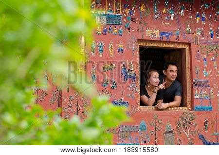 LUANGPRABANG LAOS: APRIL 22 2017 - couple on the buddhist church smiling at Wat Xieng thong temple world heritage on Aril 222017 Luang Pra bang Laos