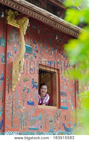 LUANGPRABANG LAOS: APRIL 22 2017 - woman on the buddhist church smiling at Wat Xieng thong temple world heritage on Aril 222017 Luang Pra bang Laos