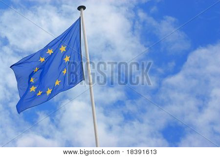 waving flag of the european union with a blue sky with fluffy white clouds on the background