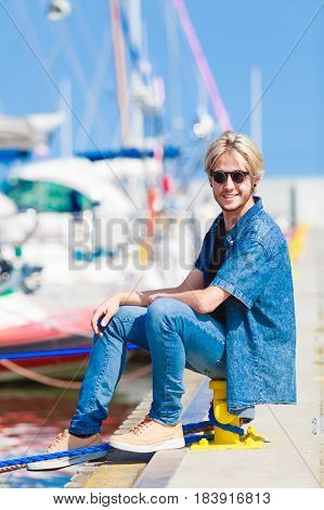 Vacation relaxation concept. Young fashionable blonde man sitting near harbor relaxing and enjoying sunny weather. Outdoor shot
