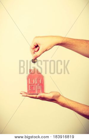 Household savings and finances economy concept. Man putting money coin into piggy bank in shape of house studio shot on light background