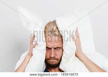 Angry Man Closing Ears With Pillows