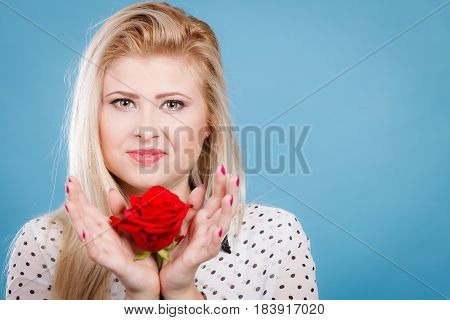 Woman holding red rose. Lovely blonde young female with flower studio shot on blue. Romance holidays valentine day concept