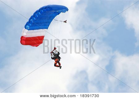 parachutist on colorful parachute floating in the air