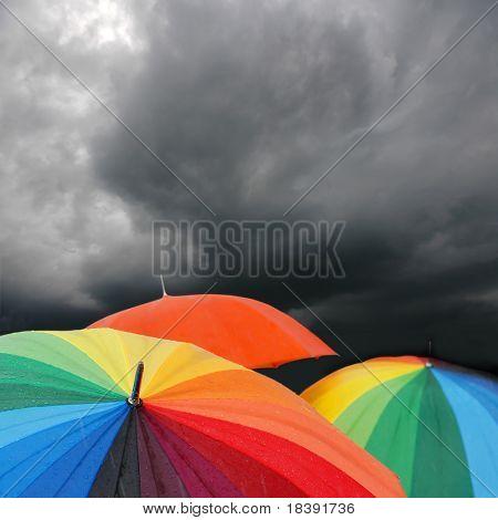 Paraguas de arco iris en las nubes de tormenta
