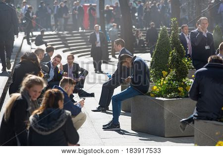 London, UK - March 15, 2017: Lots of office people relaxing in the park in the City of London during lunch time. People spending time with mobile phones. Modern busy business life